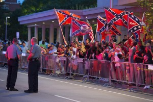 Photo by Evan Vucci/AP People wave Confederate flags outside the hotel that President Barack Obama is staying the night, on Wednesday, July 15, 2015, in Oklahoma City.  Obama is traveling in Oklahoma to visit El Reno Federal Correctional Institution. (AP Photo/Evan Vucci)